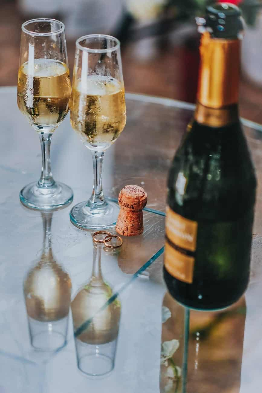 open champagne bottle near two cocktail glasses